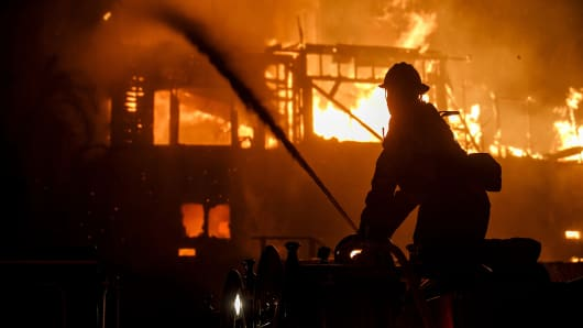 Firefighters work to put out flames after it has engulfed a home on December 5, 2017 in Ventura, California.
