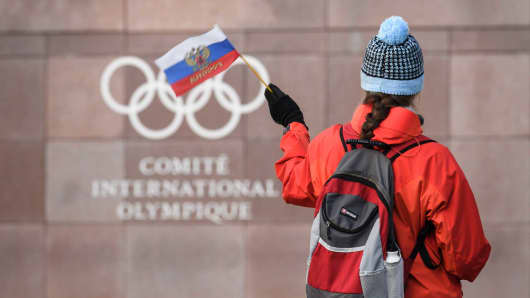 A supporter waves a Russian flag in front of the logo of the International Olympic Committee (IOC) at their headquarters on December 5, 2017 in Pully near Lausanne, Switzerland.