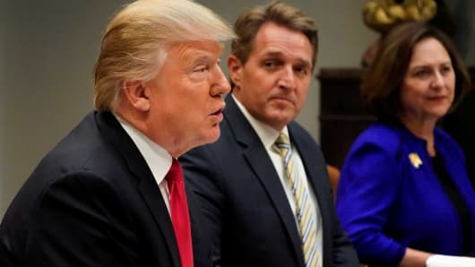 President Donald Trump, flanked by U.S. Senator Joni Ernst, Senator Jeff Flake and Senator Deb Fischer, speaks to reporters prior to a lunch meeting with Senate Republicans at the White House in Washington, December 5, 2017.