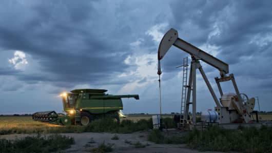 A combine harvester drives past a pumpjack in the Bemis-Shutts oil field in Kansas, U.S., on June 28, 2017.