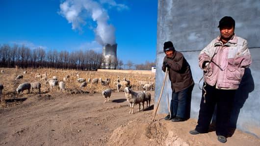 Farmers watch their sheep graze on a farm near a coal power plant in Baotou, Inner Mongolia, China.