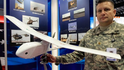 U.S. Army Major Rod Secor poses with a AeroVironment RQ-11 Raven, a small hand-launched remote-controlled unmanned aerial vehicle (SUAV), at the U.S. military booth at the Singapore Airshow in Singapore.