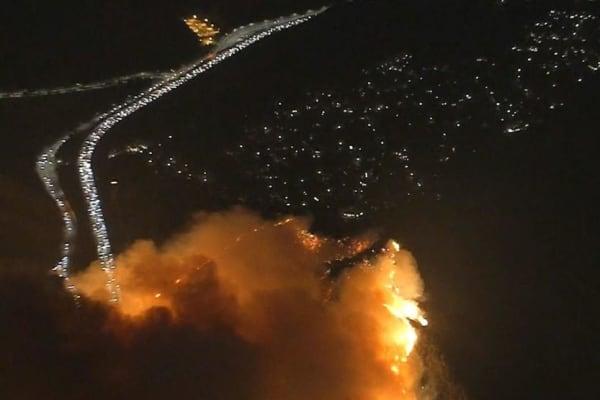 The Skirball Fire burns hillside, closing lanes on 405 North near Getty Center, threatening homes