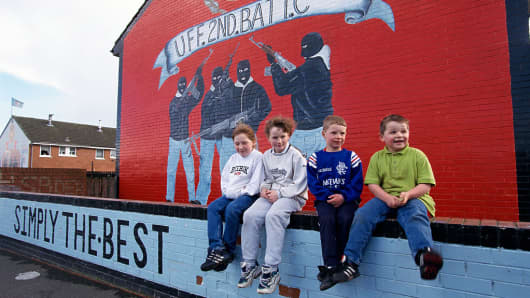 Four boys sitting beneath a unionist mural showing four masked unionist fighters in Belfast. The Northern Ireland peace talks have inspired many murals around the country, where unionists often feel the peace agreement is a betrayal and a sell out to the IRA.