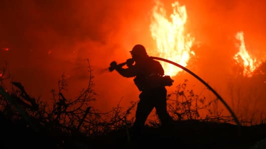 A firefighter battles a wildfire as it burns along a hillside near homes in Santa Paula, California, on December 5, 2017.