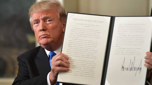 President Donald Trump holds up a signed proclamation after he delivered a statement on Jerusalem from the Diplomatic Reception Room of the White House in Washington, DC on December 6, 2017.