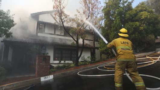 A firefighter sprays water on a burning home in the wealthy Bel-Air neighborhood during the Skirball Fire on December 6, 2017 in Los Angeles, California. Strong Santa Ana winds are rapidly pushing multiple wildfires across the region, expanding across tens of thousands of acres and destroying hundreds of homes and structures.