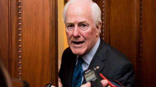 Sen. John Cornyn, R-Texas, speaks with reporters about the tax reform plan between votes in the Capitol on Thursday, Nov. 30, 2017.