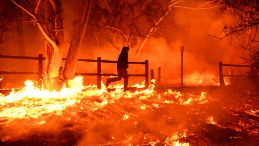 A man runs through flames to save his cats at his mobile home along Highway 33 in Casita Springs in Ventura County, California, during the Thomas Fire on Dec. 5, 2017.