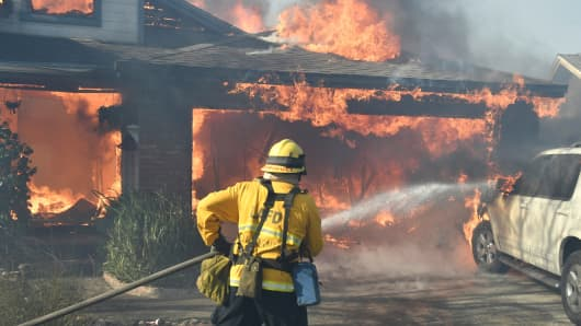 Firefighters battle to save one of many homes burning in an early-morning Creek Fire that broke out in the Kagel Canyon area in the San Fernando Valley north of Los Angeles, in Sylmar, California, U.S., December 5, 2017.