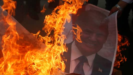 A Palestinian protester burns a poster depicting President Donald Trump during a protest against Trump's decision to recognize Jerusalem as the capital of Israel, in Gaza City.