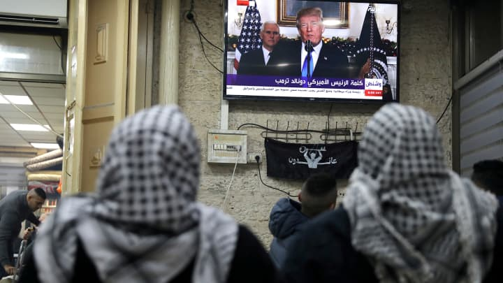 Palestinians watch a televised broadcast of President Donald Trump delivering an address, in Jerusalem's Old City.