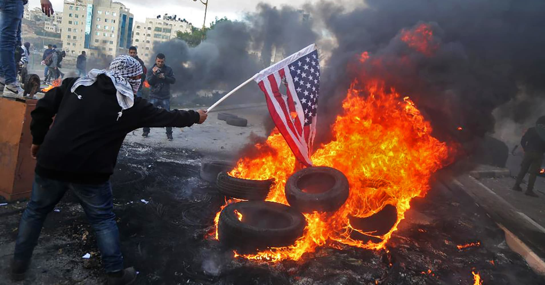 A Palestinian protester sets alight an America flag during clashes with Israeli troops at a protest against US President Donald Trump's decision to recognize Jerusalem as the capital of Israel, near the Jewish settlement of Beit El, near the West Bank city of Ramallah on December 7, 2017.