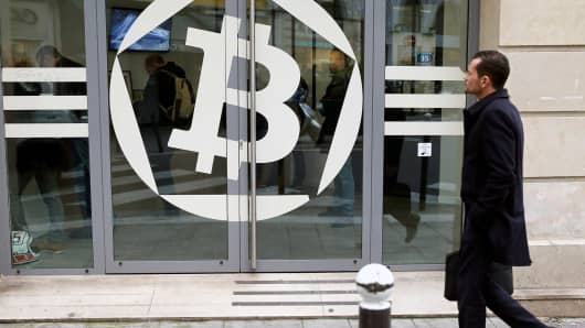 A man walks past a Bitcoin symbol on a window of the offices of the bank 'La Maison du Bitcoin' in Paris.