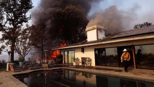 A firefighter walks near a swimming pool as a home is in flames from the Skirball fire along Linda Flora Drive on December 6, 2017 in Bel-Air, California.