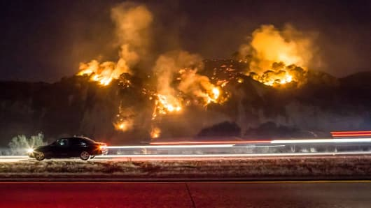 A car drives past as the Thomas Fire burns a hillside south of Casitas Springs, California, December 6, 2017.