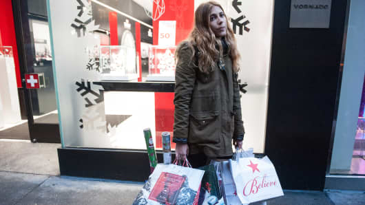 A shopper holds a number of gift bags along Fifth Ave.