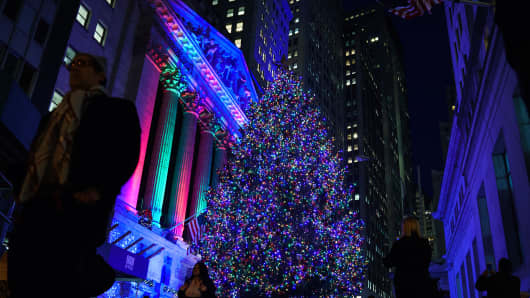 The New York Stock Exchange (NYSE) and a Christmas tree are illuminated in the Financial District.