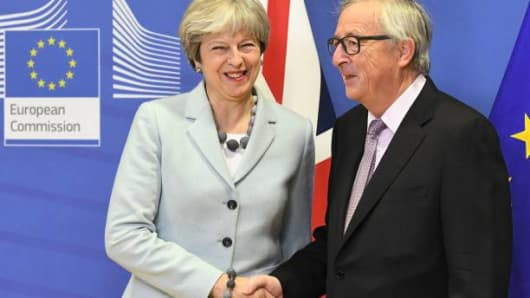 British Prime Minister Theresa May (L) is welcomed by European Commission Jean-Claude Juncker at European Commission in Brussels on December 8, 2017.