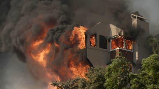 A home burns during a wind-driven wildfire in Ventura, California, U.S., December 5, 2017.