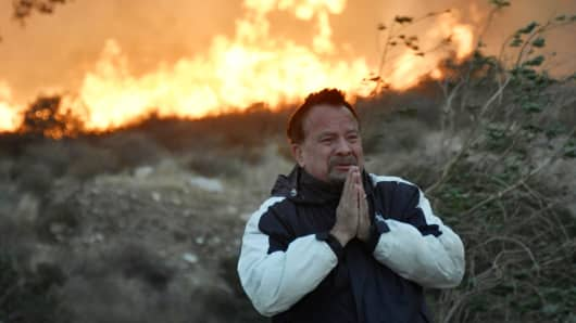 A local man tries to cope and prays during an early-morning Creek Fire that broke out in the Kagel Canyon area in the San Fernando Valley north of Los Angeles, in Sylmar, California, U.S., December 5, 2017.