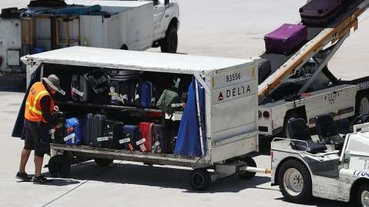 A Delta Airlines Worker Is Seen As Luggage Loaded Onto The Plane At Fort
