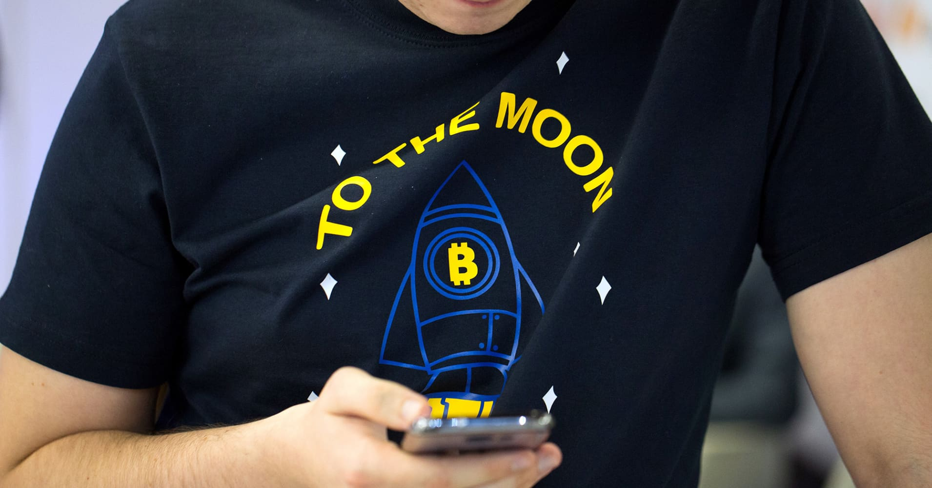 An attendee wearing a t-shirt decorated with a bitcoin rocket illustration and the words 'To the Moon' checks his smartphone at the CrytoSpace conference in Moscow, Russia, on Friday, Dec. 8, 2017.