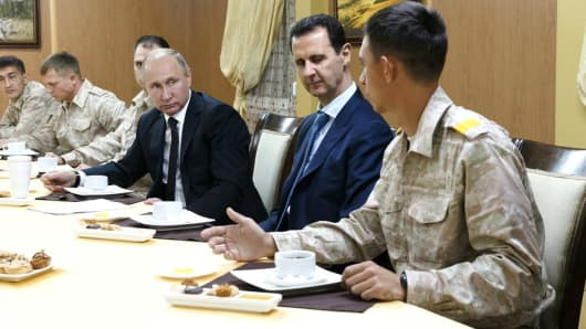 Russian President Vladimir Putin (3 R) meets with President of Syria, Bashar al-Assad (2 R) during his visit at the Hmeymim base in Syria's Latakia on December 11, 2017.