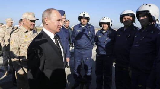 Russian President Vladimir Putin (C, front) meets with servicemen as he visits the Hmeymim air base in Latakia Province, Syria December 11, 2017.