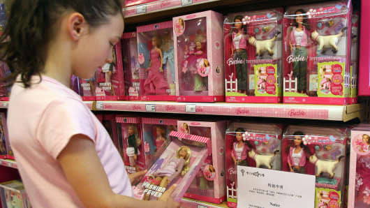 A young girl holds a Barbie doll next to a notice saying that the toy 'Barbie and Tanner' made by US toy giant Mattel.