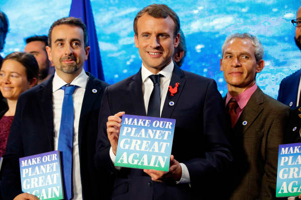 French President Emmanuel Macron holds a sign with the slogan 'Make our planet great again' as he attends the 'Tech for Planet' event at the 'Station F' start-up campus ahead of the One Planet Summit in Paris on December 11, 2017.