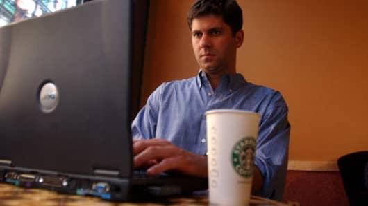 A man uses the Internet on his laptop computer at a Starbucks coffee shop in New York City.