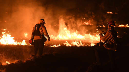 Firefighters light backfires as they try to contain the Thomas wildfire which continues to burn in Ojai, California on December 9, 2017.