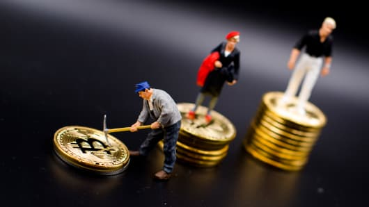A miner miniature figures near Bitcoin physical coin. Futures on Bitcoins increased by more than 20% after their American debut on the Chicago Cboe Futures Exchange.