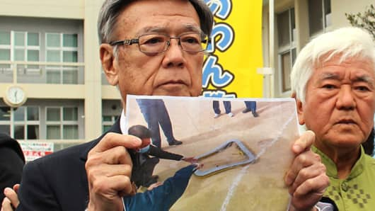 Okinawa Governor Takeshi Onaga shows a photo of a window claimed to have fallen from a U.S. helicopter.