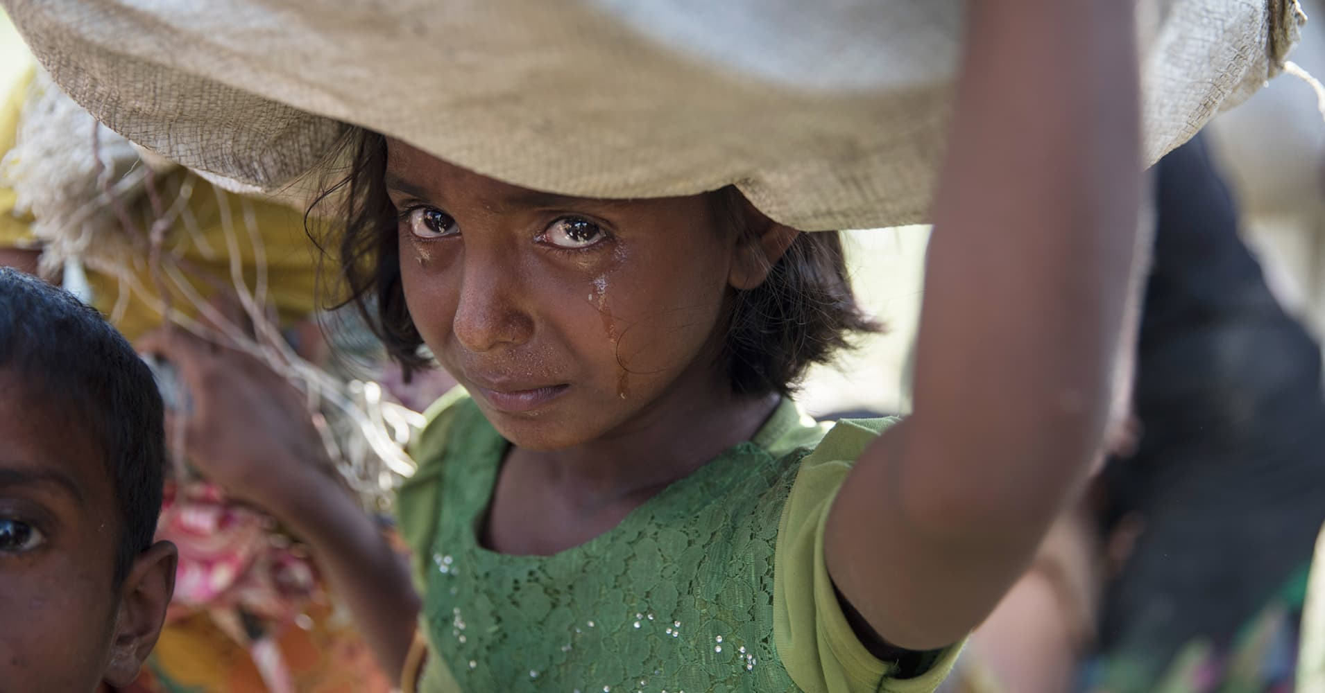 A Rohingya girl cries as refugees fleeing from Myanmar cross a stream in the hot sun on a muddy rice field on October 16, 2017 near Palang Khali, Cox's Bazar, Bangladesh.