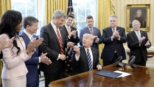 President Donald Trump gives the pen to Rep. Bill Huizenga (R-MI) after signing H.J. Res. 41 in the Oval Office of the White House on February 14, 2017 in Washington, DC.
