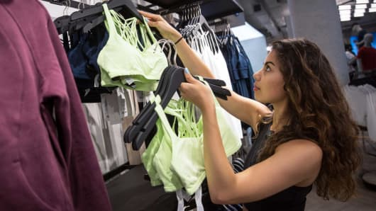 An employee restocks clothes on display at the Lululemon Athletica sports apparel store on Regent Street in London.