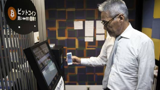 An employee uses a smartphone as he demonstrates how to purchase bitcoins from a bitcoin automated teller machine (ATM) at the Coin Trader bitcoin retail store in Tokyo, Japan, Aug. 30, 2017.