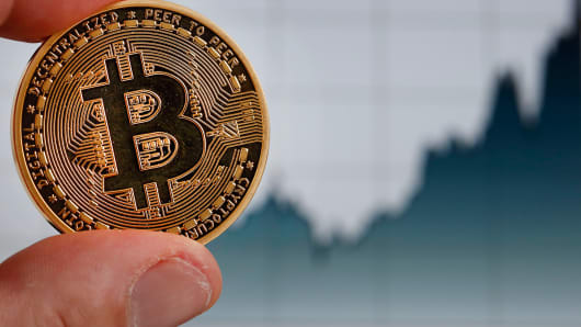 In this photo illustration, a visual representation of the digital Cryptocurrency, Bitcoin in front of a Bitcoin chart is displayed on November 30, 2017 in Paris, France.