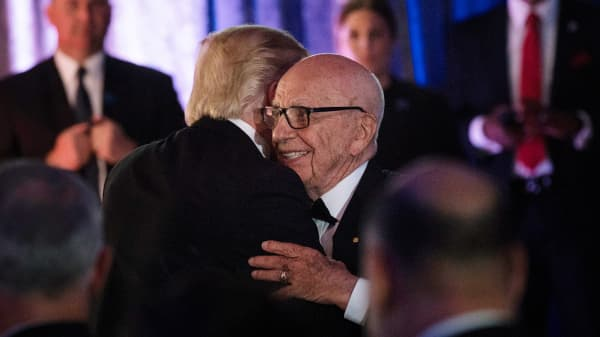 President Donald Trump (L) is embraced by Rupert Murdoch, Executive Chairman of News Corp.