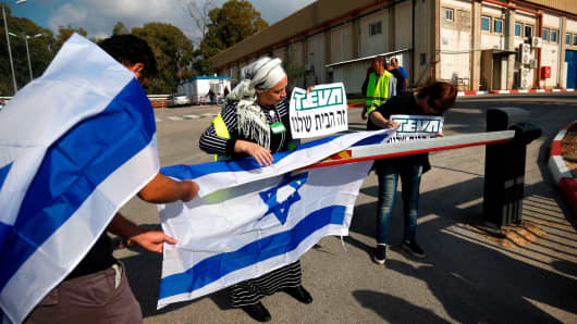 Israeli employees of Teva, the world's biggest manufacturer of generic drugs, protest outside the pharmaceutical company's plant in Kiryat Shmona, in northern Israel, on December 14, 2017.