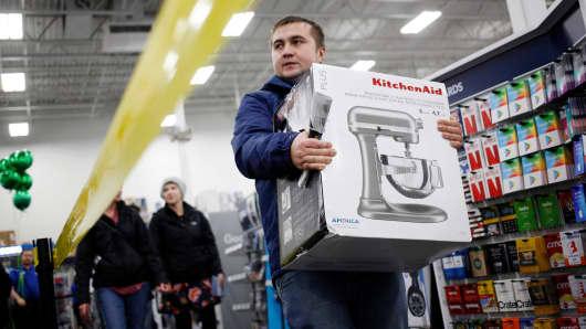 A shopper carries a Whirlpool KitchenAid mixer inside a Best Buy store in Louisville, Kentucky.