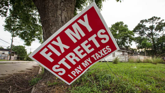 'Fix our streets' sign, next to a blighted home in the 9th Ward in New Orleans.
