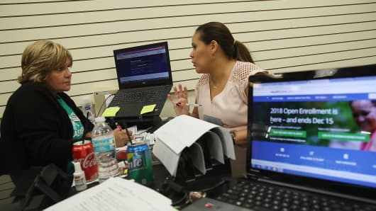 An insurance agent from Sunshine Life and Health Advisors, speaks with a customer as she shops for insurance under the Affordable Care Act at a store setup in the Mall of Americas in Miami, Florida.