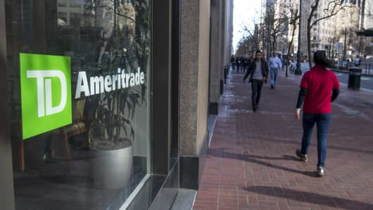 Pedestrians pass in front of a TD Ameritrade location in San Francisco, California.