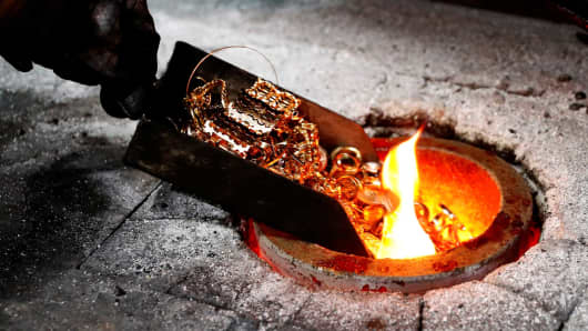 A worker places gold jewelery into a melting furnace at the Austrian Gold and Silver Separating Plant in Vienna, Austria.