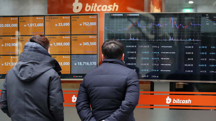 Pedestrian look at monitor showing the prices of virtual currencies at the Bithumb exchange office in Seoul, South Korea, on Friday, Dec. 15, 2017.