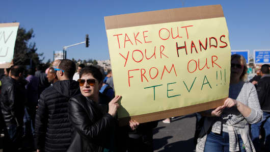 Israeli employees of Teva, the world's biggest manufacturer of generic drugs, hold placard during a protest in the centre of Jerusalem on December 17, 2017, against plans by the pharmaceutical giant to shed employees