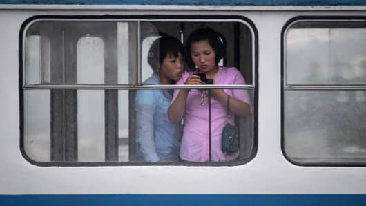 Women look at a mobile phone as they ride a tram in Pyongyang, North Korea.